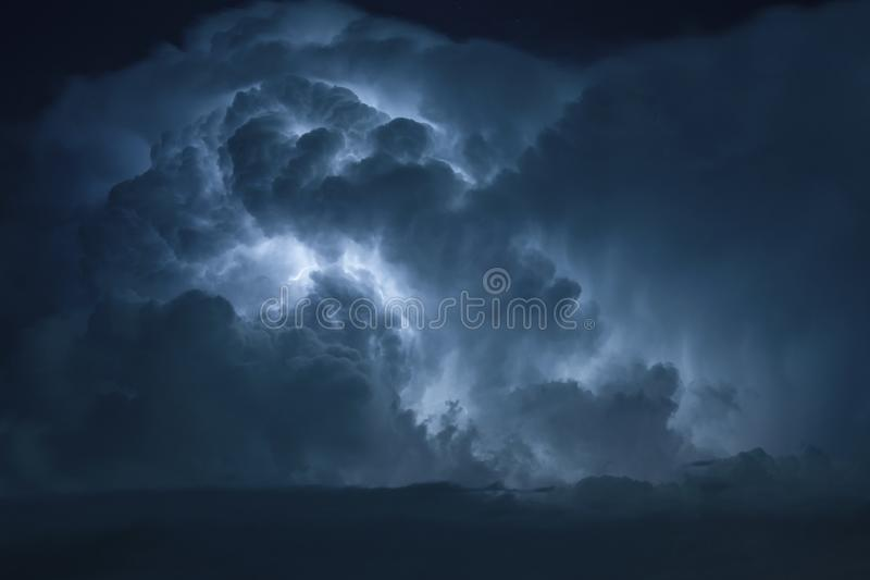 Blue Lightning strike surrounded by storm clouds. royalty free stock photo