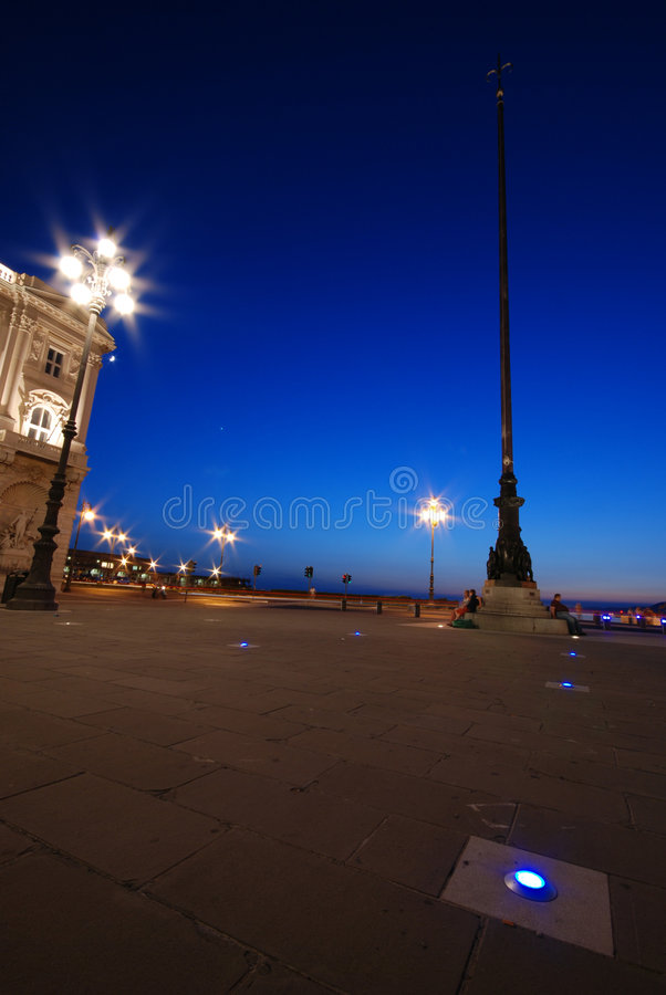 Blue lights and the mast pole. Piazza Unità d'Italia with illuminated buildings and pole decorations at dusk / night - Trieste - Italy 2007 royalty free stock photo