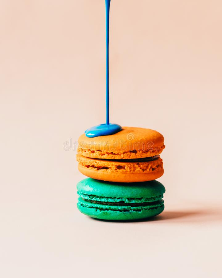 Blue liquid paint spills over the macaroons stock images