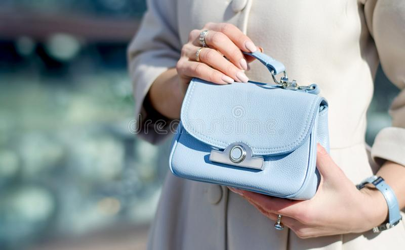 Blue little handbag in female hands. Close-up leather handbag. Women walking in the city. Girl in a beige coat royalty free stock images