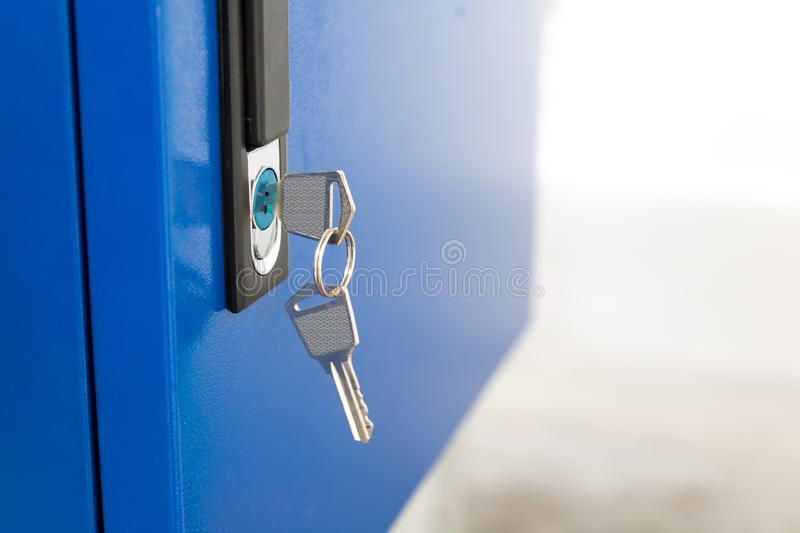 Blue locker and key chain in school gym. Modern metal cabinets and copyspace for your design stock photos