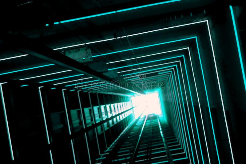 Blue Luminous Lift Tunnel. Elevator corridor in the building lit by Blue elumination. Futuristic elevator shaft is located in a high tower. Lift shaft in a stock photography