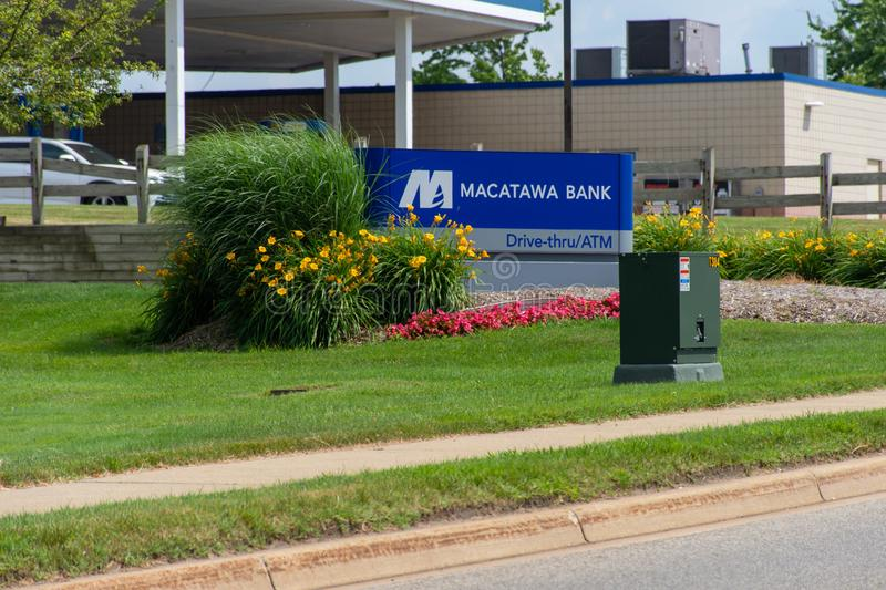 Blue Macatawa Bank Sign with drive thru, atm and flowers on green grass and blue sky stock images