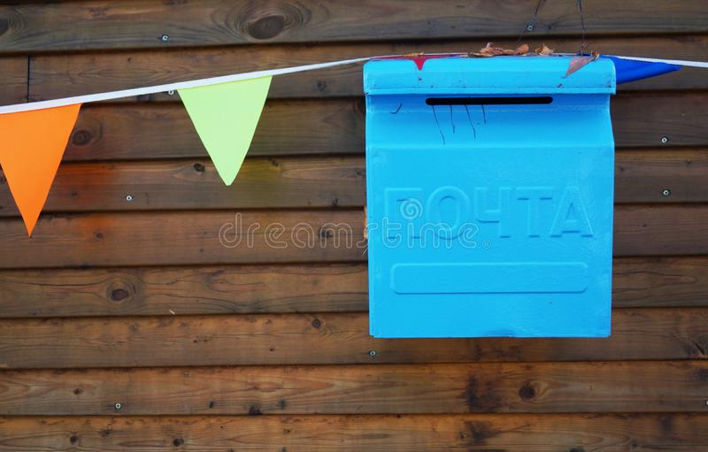 Blue mailbox on a brown wooden background royalty free stock photo