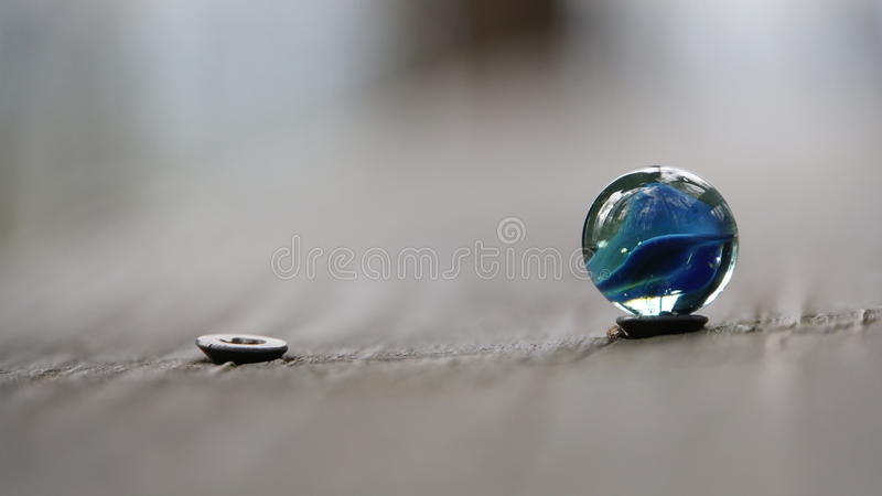 Blue marble ball standing on the head stock images