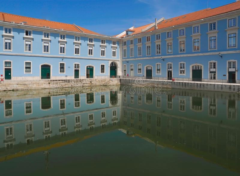 Blue marine administration building mirrors in water. Beautiful blue marine administration building in Lisbon royalty free stock image