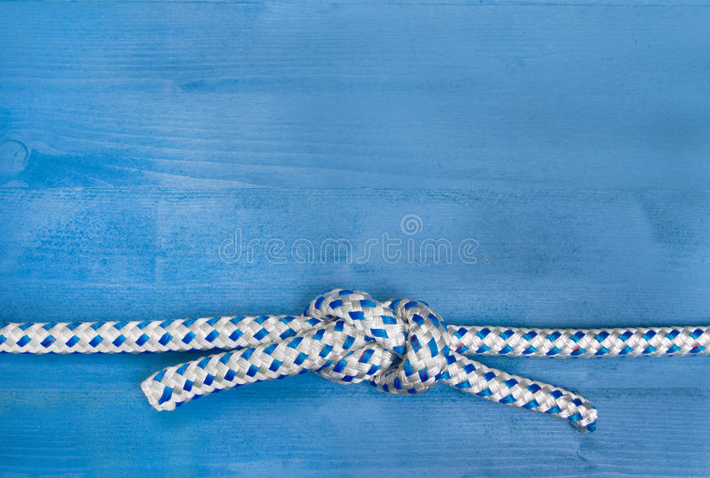 Blue maritime background. Wooden blue maritime background with a sailor knot royalty free stock image