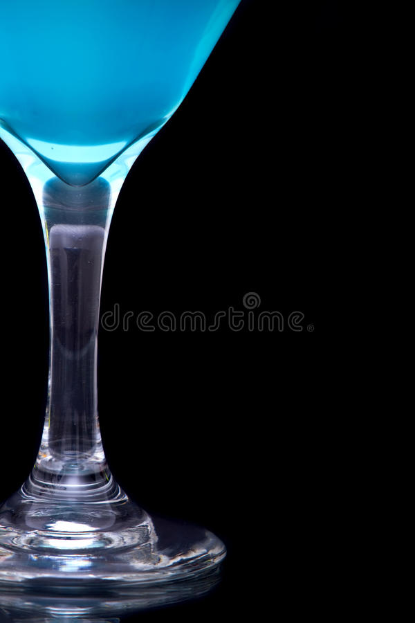 Blue martini in glass. Blue martini cocktail in glass over black background royalty free stock photo