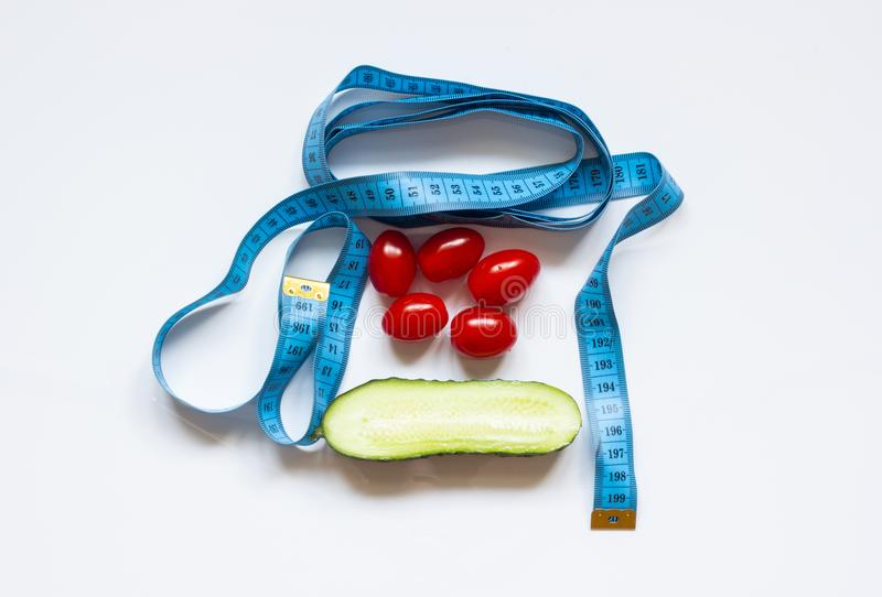 Blue measuring tape with tomato and cucumber on a white background stock image