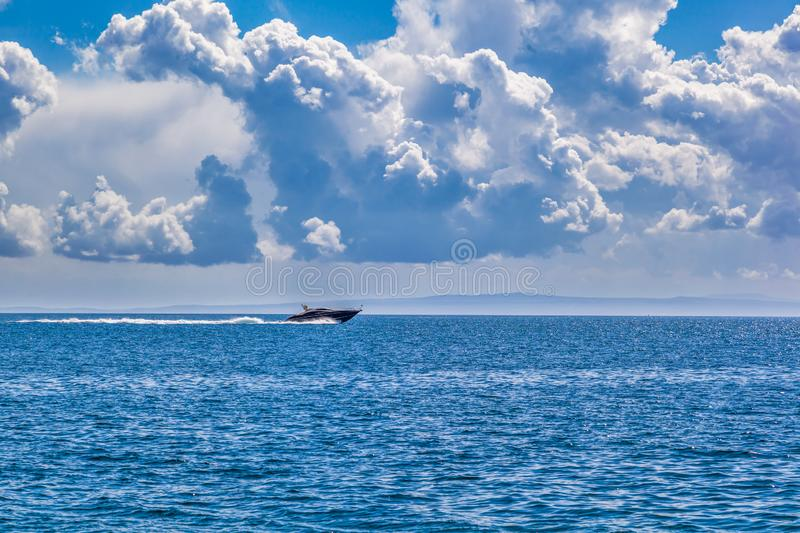 Speed boat on blue sea with cloudy sky stock photo