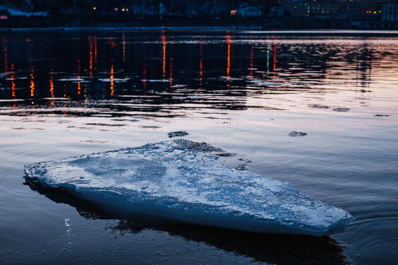 Blue melting ice floe floating in the river. In the city stock photos