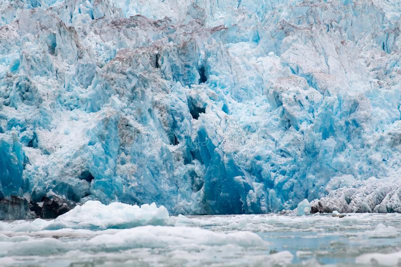 Blue Melting iceberg flowing into Alaskan sea. Alaskan sea and ocean cruise with icebergs and glaciers blue melting shrinking global warming climate change stock photography