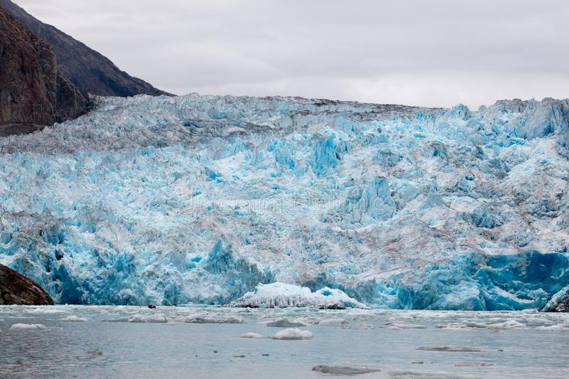 Blue Melting iceberg flowing in Arctic sea. Alaskan sea and ocean cruise with icebergs and glaciers blue melting shrinking global warming climate change stock image