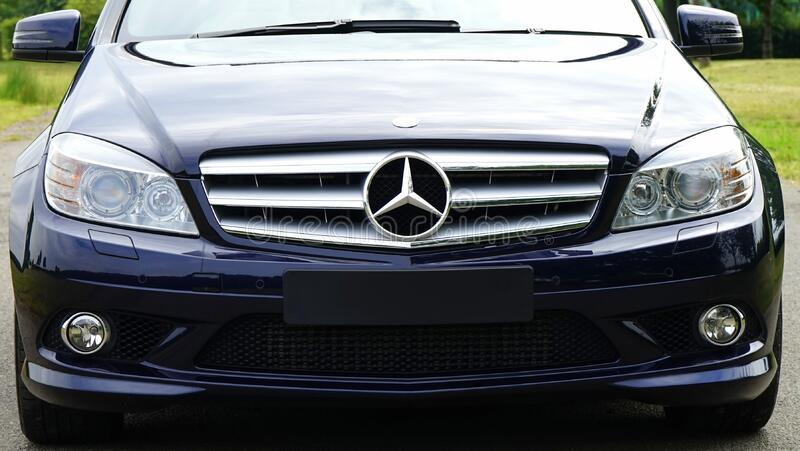 Blue mercedes Sedan Near Green Grass Field during Day Time royalty free stock photography