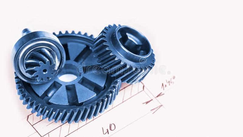 Blue metal gearwheels with a technical drawing in background. Abstract industrial background with mechanical engineering theme from cogwheels stock photography