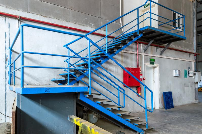 Blue metal ladder in an old factory. Red fire box and fire tube on the wall stock image