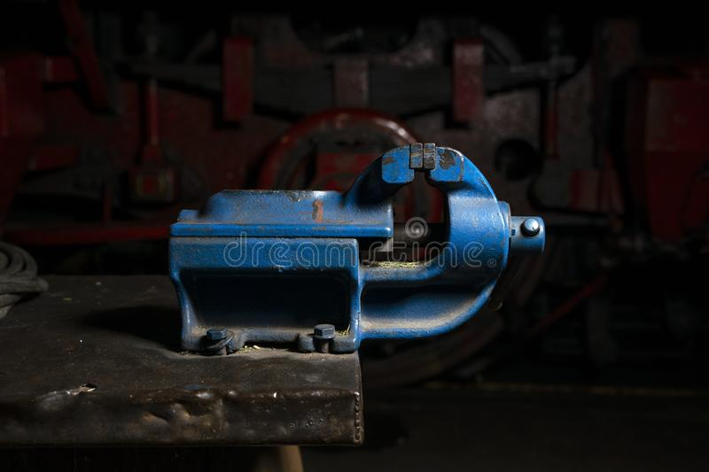 Blue metal mechanical vise mounted on a workbench in the repair shop stock photo