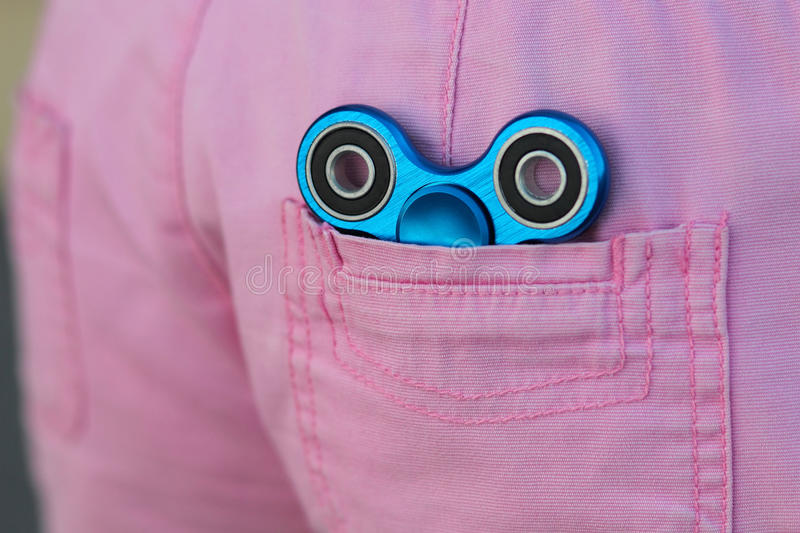 Blue metal popular fidget spinner in the back pocket of pink jeans, anxiety relief toy, anti stress and relaxation fidgets stock photos