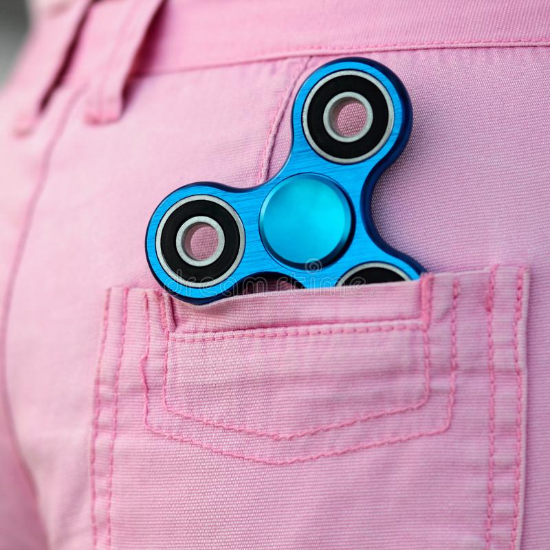 Blue metal popular fidget spinner in the back pocket of pink jeans shorts, anxiety relief toy, anti stress and relaxation fidgets.  stock images