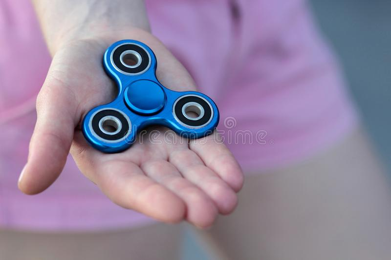 Blue metal popular fidget spinner toy on the palm of your hand, anxiety relief toy, anti stress and relaxation fidgets.  royalty free stock photography