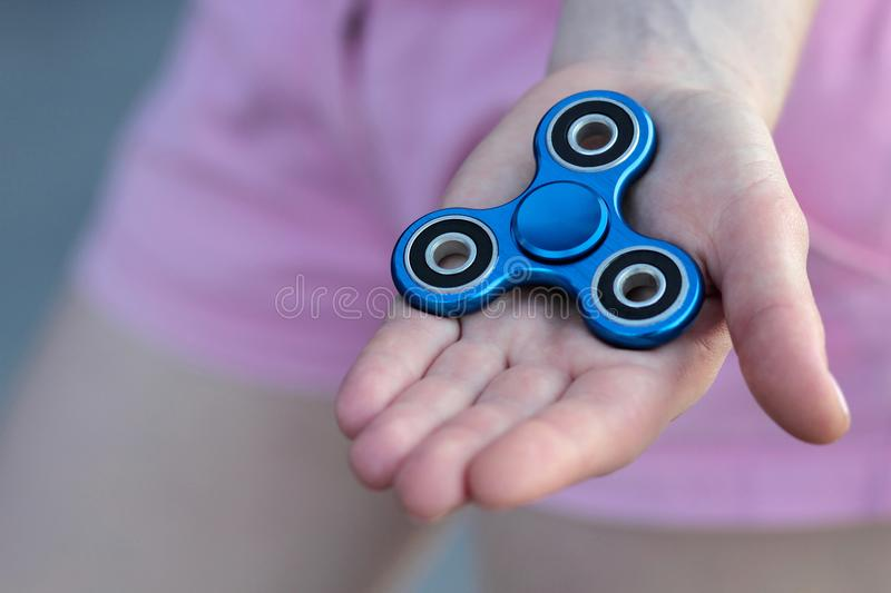 Blue metal popular fidget spinner toy on the palm of your hand, anxiety relief toy, anti stress and relaxation fidgets.  stock photography