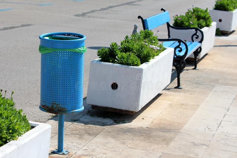 Blue metal public trash can in same row with blue wooden public bench and white concrete flower pots on stone tiles sidewalk next stock photo