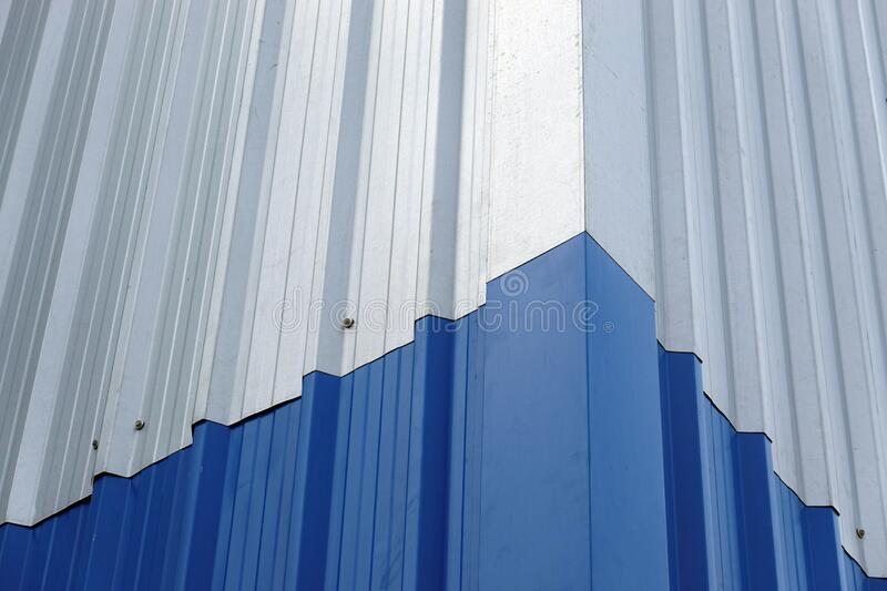 Blue Metal sheet wall panels and roofs,  Abstract background.Blue color and Silver color Metal Sheet or Blue Color and Silver. Metal sheet wall panels and roofs stock photo