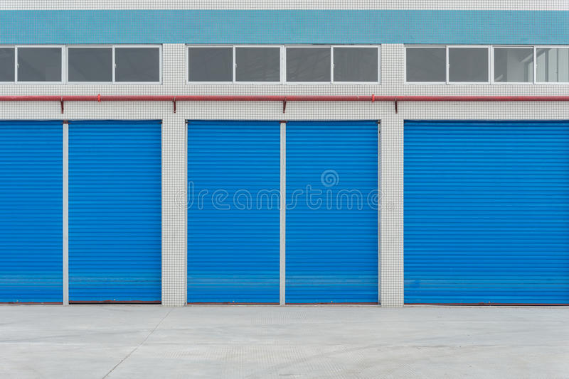 Blue metal shutter doors on commercial shop royalty free stock images