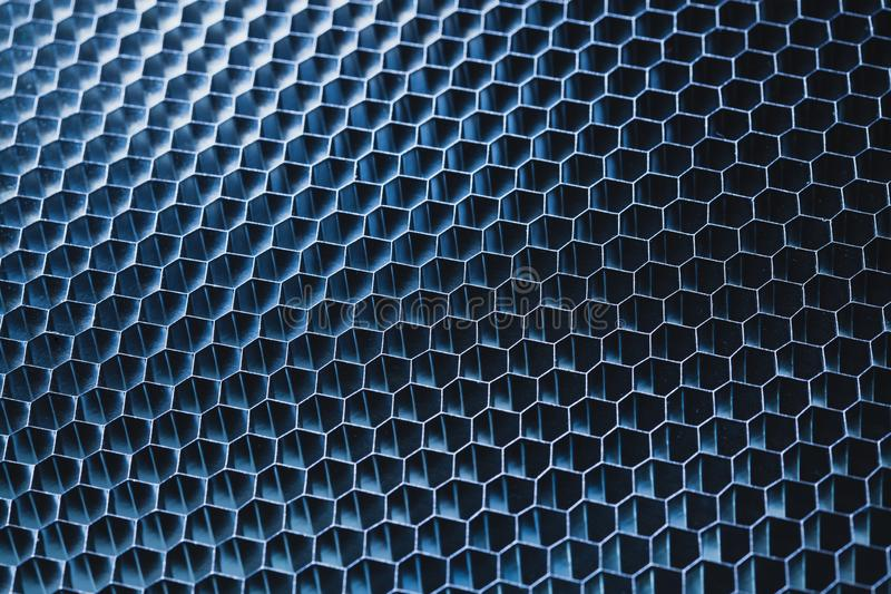 Blue metallic honeycomb grid texture pattern. Dark background stock photography