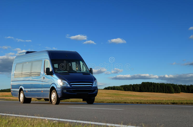 Blue minibus on highway. Blue minibus transporting passengers on highway over blue sky stock photos