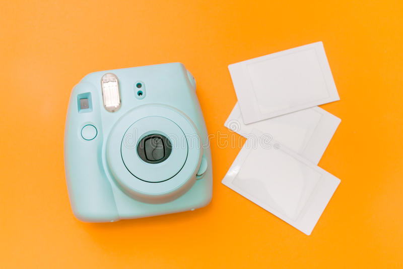 Blue mint instant camera with films. On orange background royalty free stock photos