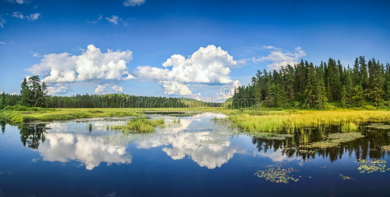 Blue mirror lake reflections of clouds and landscape. Ontario, Canada. Reflections in blue water of beautiful lake. Mirrored clouds and landscape. Ontario royalty free stock photography