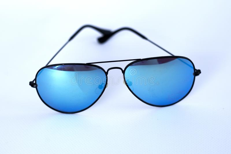 Blue mirrored sunglasses with anti-reflective coating and UV protection on a white background. royalty free stock photos