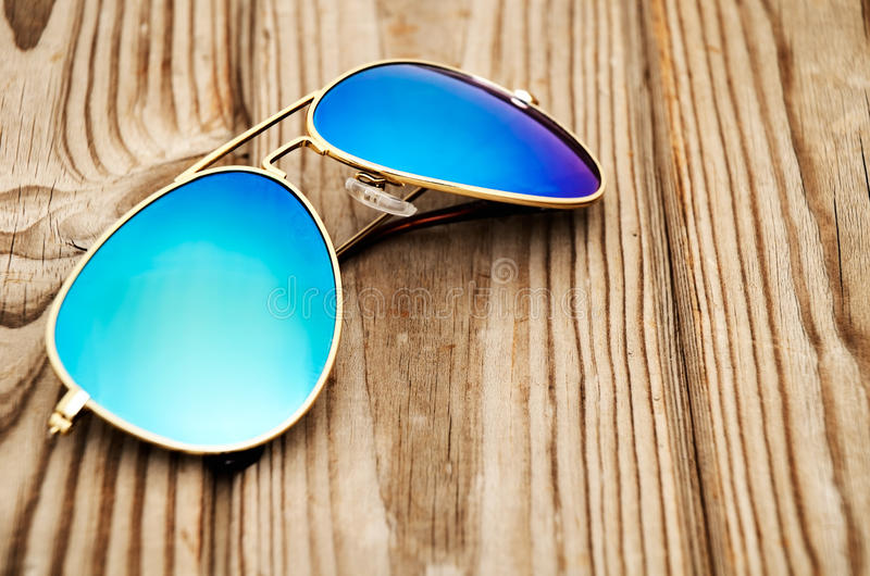 Blue mirrored sunglasses on the wooden background close up royalty free stock images
