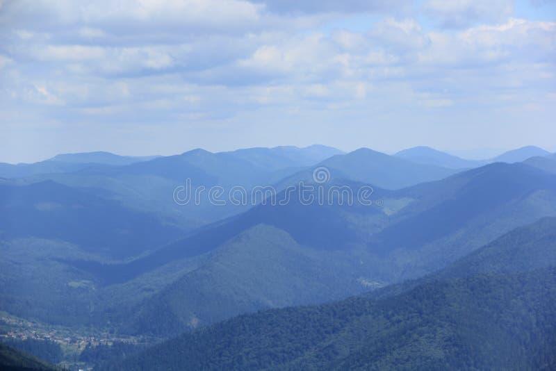 Blue misty background of Carpathian mountains and Bukovel ski resort in summer. Blue blurred misty background of Carpathian mountains and Bukovel ski resort in royalty free stock photo