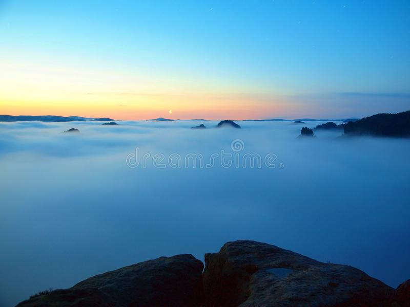 Blue misty morning, view over rock to deep valley full of light mist. Dreamy spring landscape within daybreak. Misty morning, view over rockto deep valley full royalty free stock photo