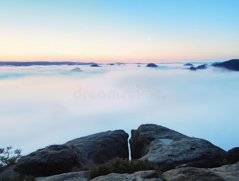 Blue misty morning, view over rock to deep valley full of light mist. Dreamy spring landscape within daybreak. Misty morning, view over rockto deep valley full royalty free stock image