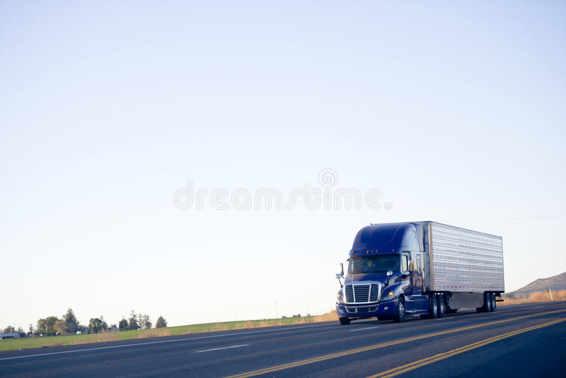 Blue modern semi truck reefer trailer carry cargo on highway. Modern huge powerful drivers popular dark blue big rig semi-truck with a sleeping compartment and a royalty free stock images