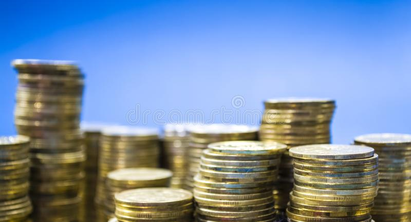 Blue monophonic background. Towers from coins. Ukrainian hryvnia. Money and finance, profit. Business. Accumulation. stock image