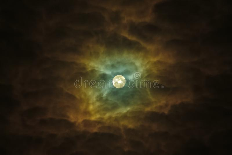 Blue Moon highlights the cloudy skies. Night Sky Sunflower. Telescope astrophotography. Bright Detailed Close-Up Blue Full Moon Ominously Highlights The Clouds royalty free stock photo