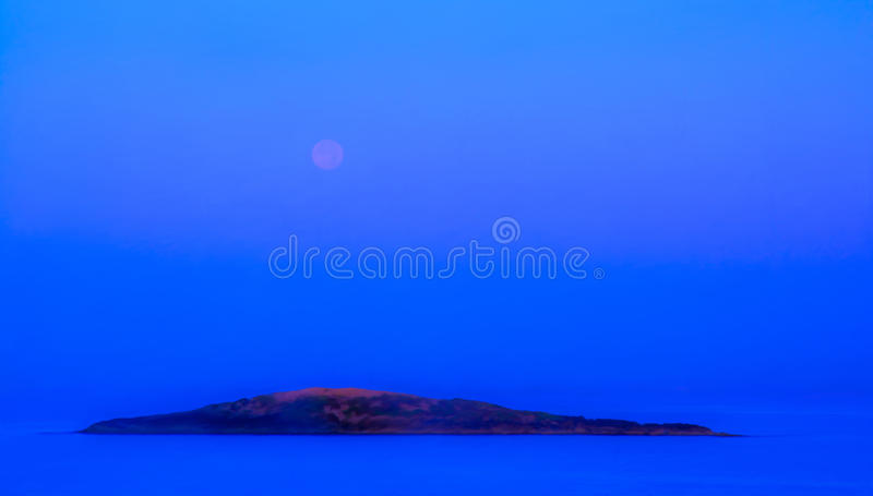 Blue moonset and sunrise. Over small island in Mallorca, Balearic islands, Spain