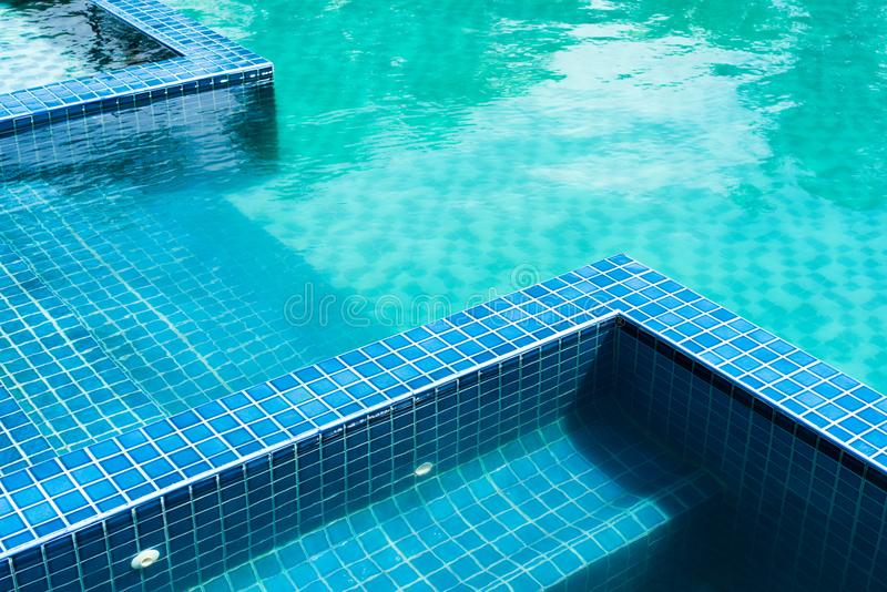 Blue mosaic tile steps in green swimming pool royalty free stock image