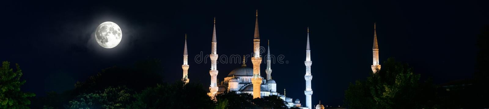 Blue Mosque or Sultanahmet at night, Istanbul, Turkey. Illuminated minarets and full moon on a dark sky background. Panoramic view of the famous mosque in stock images