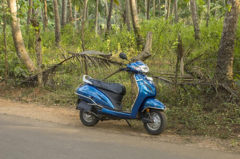Blue motorbike stands on the asphalt road against the green jungle. Querim, Goa/India - 06.12.2018: blue motorbike stands on the asphalt road against the green royalty free stock images