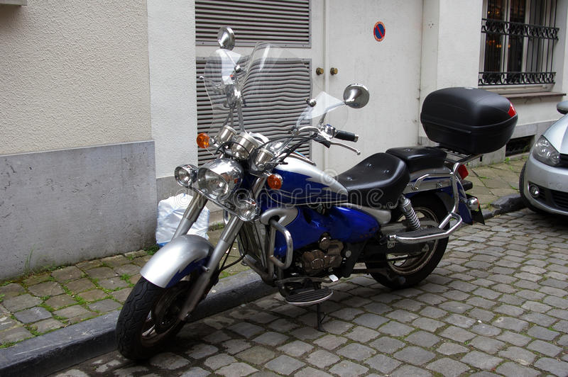 Blue motorcycle in the city;. Twin cylinder Motorcycle. Beautiful electric blue. A fine example of a well kept street bike stock image
