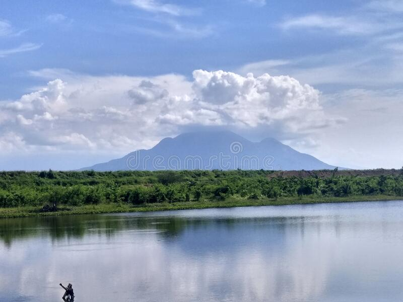 Blue mountain scenery accompanied by a small lake in an area in the city of Sidoarjo, Indonesia. Blue mountain scenery accompanied by a small lake in an area in stock photos