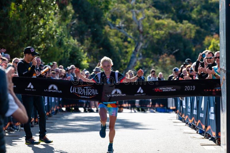 Ultra-Trail Australia UTA11 race. Runner Paige Penrose, winner of the womens event, crosses at the finish line. Blue Mountains, Australia - April 16 2019: Ultra stock images