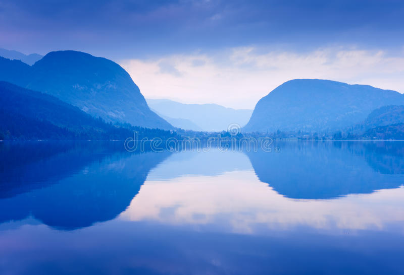 Blue mountains reflected in lake Bohinj, Slovenia. stock image