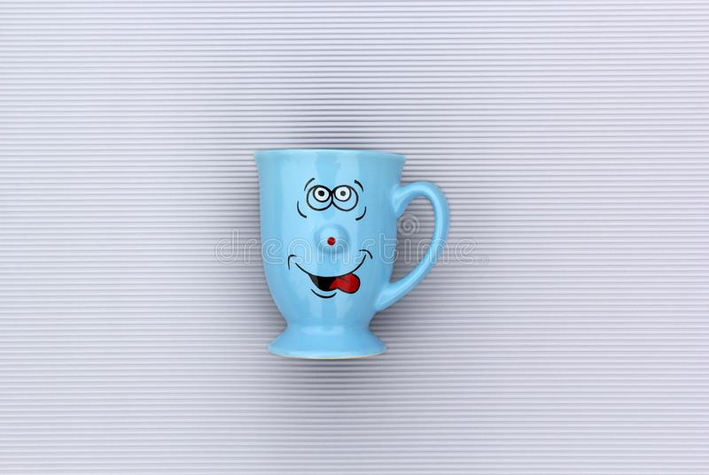Blue mug of coffee with happy smile face on gray background. Good morning, creative greeting card concept stock image