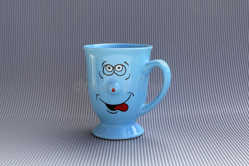 Blue mug of coffee with happy smile face on gray background. Good morning, creative greeting card concept stock photo
